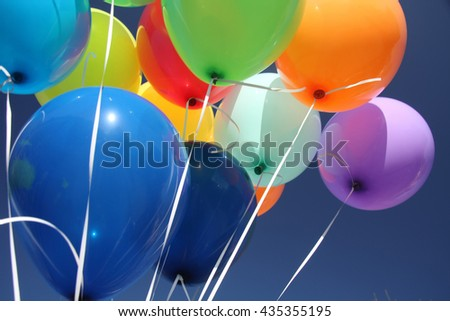 Colorful balloons dancing in a blue sky
