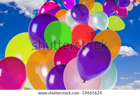 colorful  balloons floating on a blue sky with clouds - stock photo