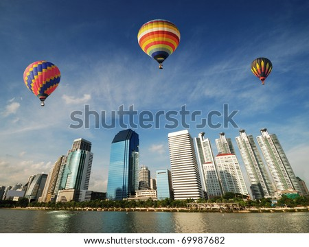 Colorful balloons floating over Bangkok skyscraper - stock photo
