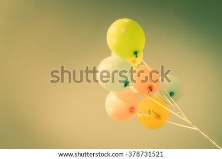 Colorful balloons on blue sky background in vintage color style - stock photo