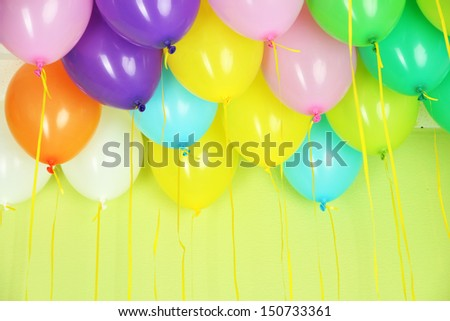 Colorful balloons on green wall background - stock photo