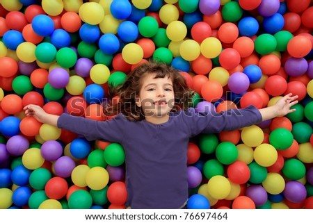 colorful balls funny park little girl lying gesturing happy - stock photo