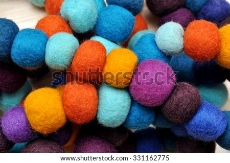 Colorful balls of wool. Colorful felt balls. Dried balls of wool. Colored beads. Felt handmade. Necklace with colorful beads - stock photo