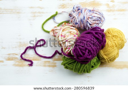 colorful balls of wool on rustic white wooden background - stock photo
