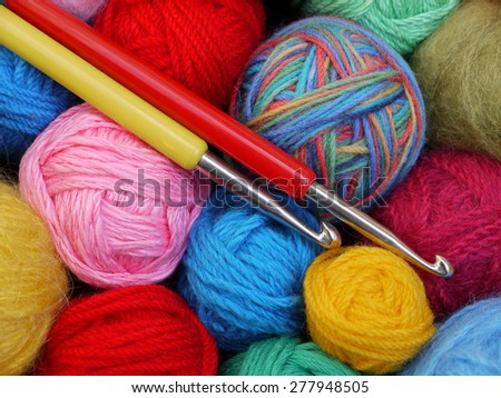 colorful balls of wool with crochet hooks