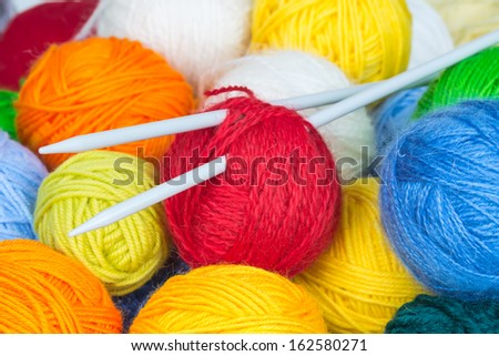Colorful balls of wool yarn and knitting needles - stock photo