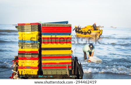 colorful baskets on the beach with fishermen on the background - stock photo