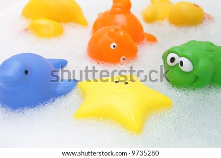 Colorful bath toys in soap water - stock photo