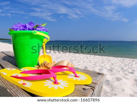 Colorful beach accessories on boardwalk by ocean - stock photo