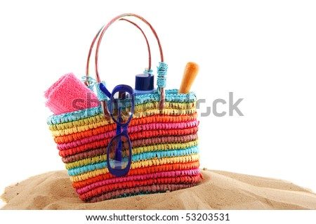 colorful beach bag with toys and sunglasses for the whole family - stock photo