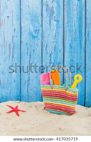 Colorful beach bag with toys at the beach - stock photo