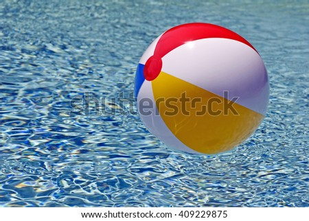 Colorful Beach Ball Floating In Blue Swimming Pool - stock photo