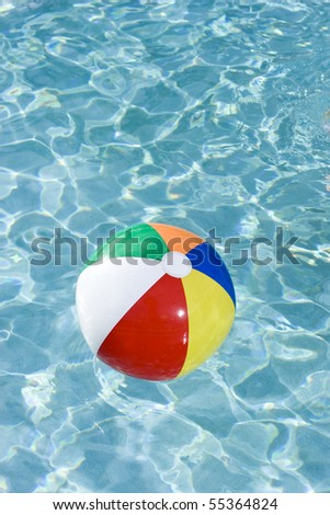 Colorful beach ball floating on surface of swimming pool water
