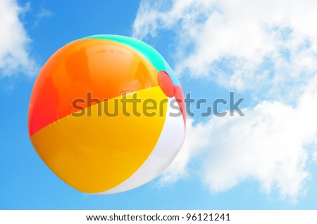 Colorful beach ball up in the air with beautiful blue sky - stock photo