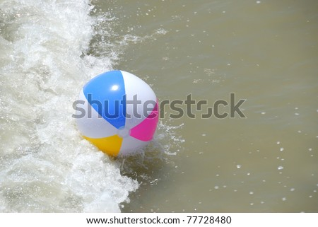 colorful beach ball washing up at the ocean surf st. augustine beach florida usa - stock photo