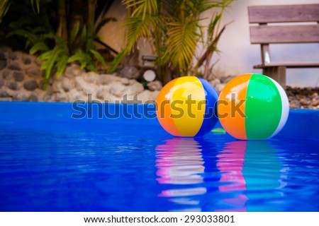 Colorful beach balls floating in pool - stock photo