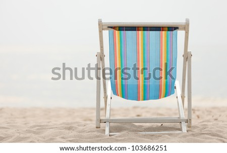 Colorful beach chair on sand with waves in background