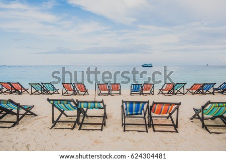 colorful beach chairs on the white sand beach with the sunset at koh Nang Yuan in Suratthani province Thailand