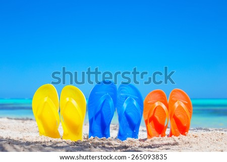 Colorful beach flip flops sandals on the beach - stock photo