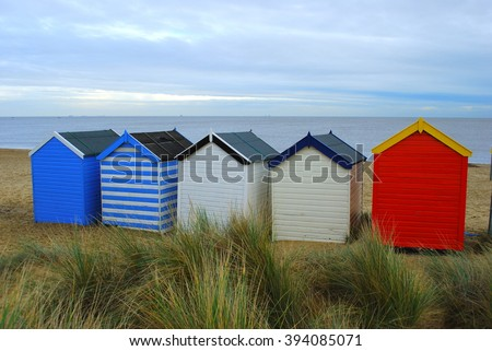 Colorful beach huts in British seaside - stock photo