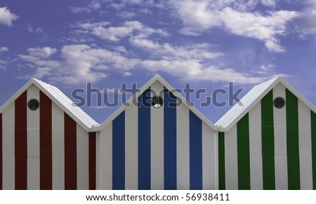 Colorful beach huts with blue sky in the back. - stock photo