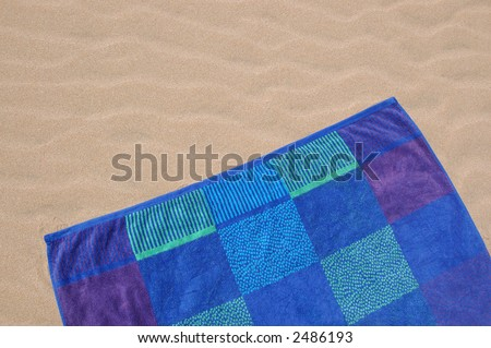 Colorful beach towel on rippled sand - stock photo