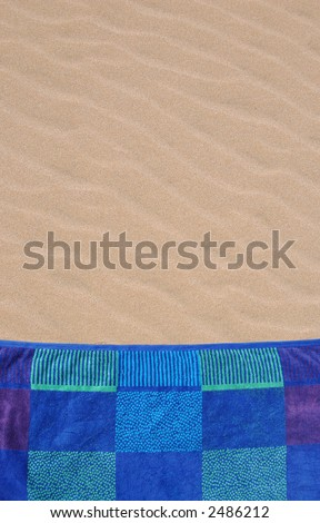 Colorful beach towel on rippled sand texture - stock photo