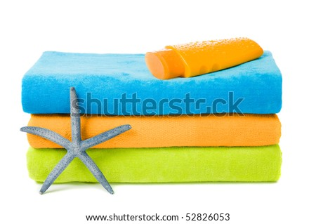Colorful beach towels with suntan lotion and starfish on white background - stock photo