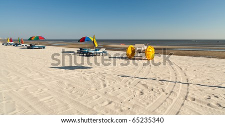 Colorful beach tricycles along the shoreline with lounge chairs and umbrellas along the Mississippi Gulf Coast. - stock photo