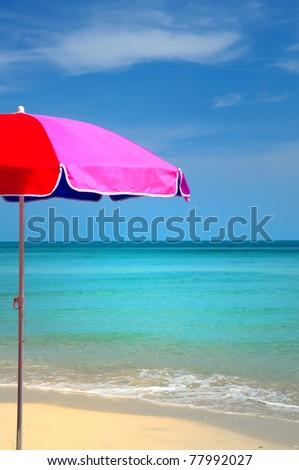 Colorful beach umbrella against sunny blue sky. - stock photo