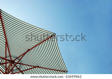 Colorful beach umbrella against the sun light - stock photo