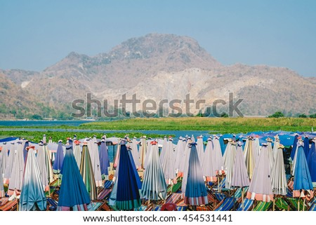 Colorful beach umbrella and chair near the sea with mountain. On the vacation - stock photo