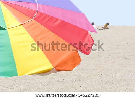 Colorful beach umbrella in the sand. Large, multicolored umbrella laying on a sandy beach.Green, red, blue, orange, purple colors.Blue sky.Blurred background showing children playing in the sand. - stock photo