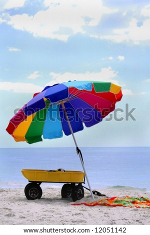 Colorful Beach Umbrella on Beach with Towel and Wagon - stock photo