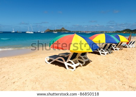 Colorful beach umbrellas on a Caribbean beach - stock photo