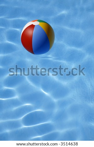 Colorful beachball floating in bright blue pool - stock photo