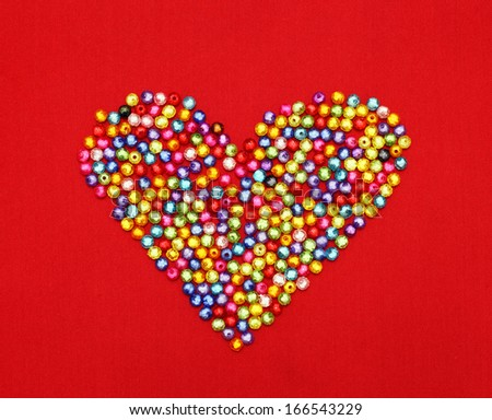 Colorful beads heart shape isolated on red background