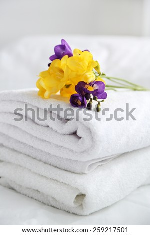 Colorful beautiful freesias on fresh towels in hotel, close up - stock photo