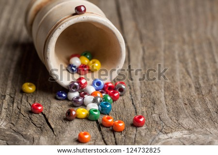 colorful beautiful glass beads with ceramic glass on old wooden table - stock photo