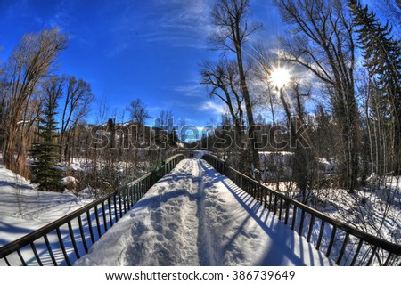 Colorful beautiful view of a snowy bridge with the sun above in the winter with golden trees landscape in Aspen ,Colorado with blue HDR sky through fisheye lens, USA - stock photo