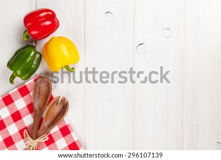 Colorful bell peppers and kitchen utensil on white wooden table. Top view with copy space - stock photo