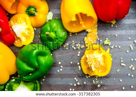 Colorful Bell Peppers on the Chopping Board, Cut with Seeds all over the Board. Top View. - stock photo