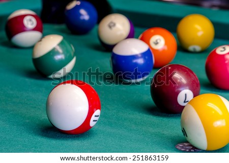 Colorful billiard balls sitting on pool table with eight ball in front