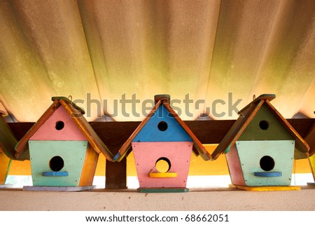 Colorful bird houses under the roof with nice lighting and leading lines - stock photo