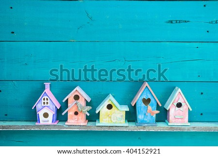 Colorful birdhouses with butterfly on shelf by antique rustic teal blue wood background; pink, purple, yellow, orange birdhouses - stock photo