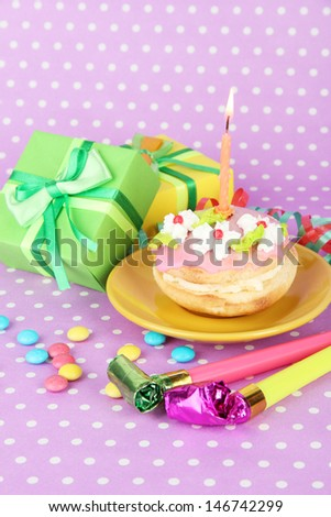 Colorful birthday cake with candle and gifts on pink background