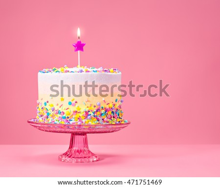 Colorful Birthday cake with sprinkles on a pink background.