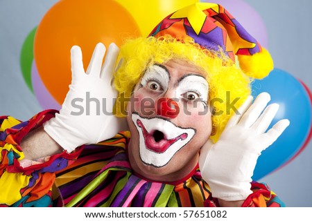 Colorful birthday clown making a funny face. - stock photo