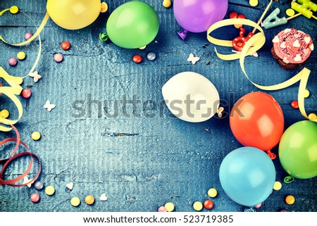 Colorful birthday frame with multicolor party items on dark blue background. Happy birthday concept with copy space