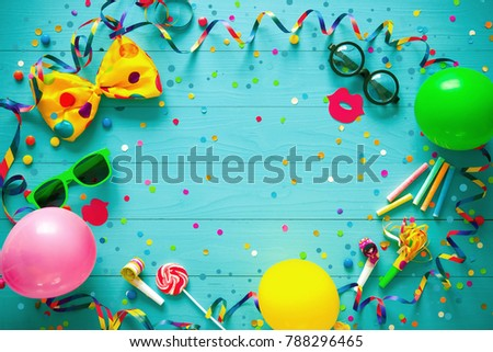 Colorful birthday or carnival frame with party items on wooden background